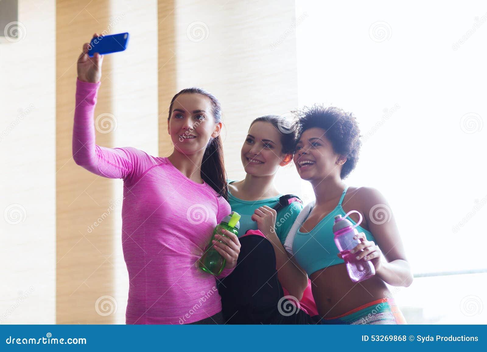 Gelukkige vrouwen die met smartphone selfie in gymnastiek nemen