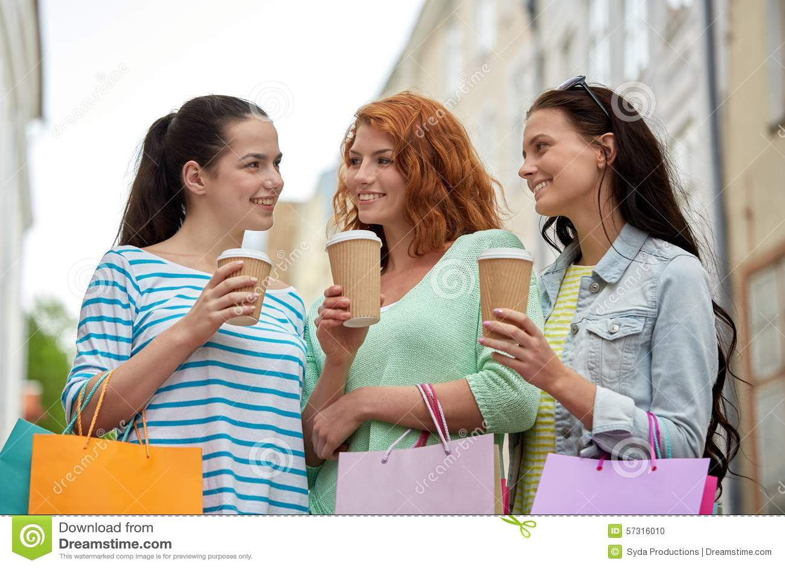 Gelukkige vrouwen met het winkelen zakken en koffie in stad