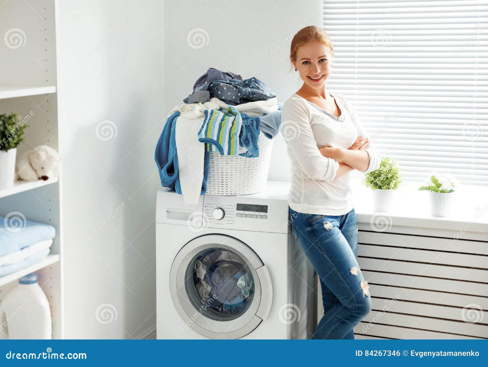 Gelukkige vrouwenhuisvrouw in de wasserijruimte dichtbij wasmachi