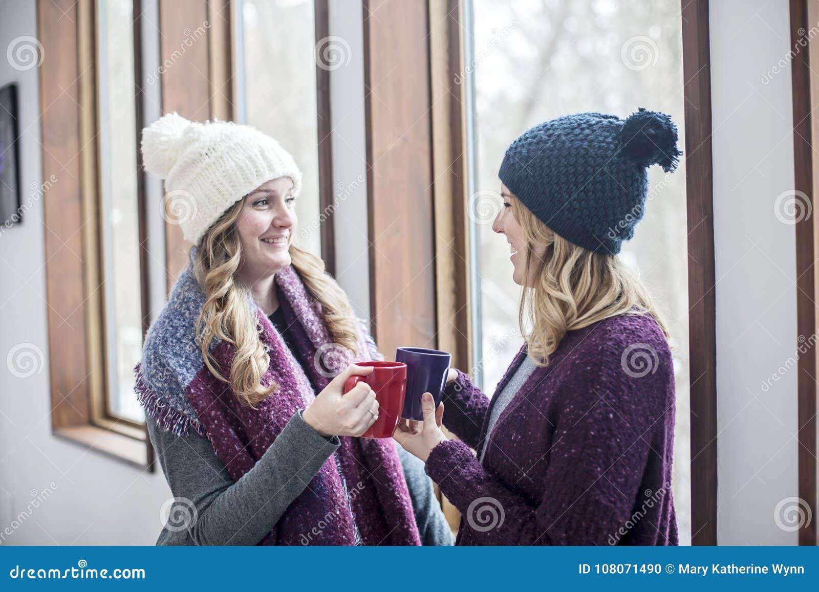 Gelukkige vrouwenvrienden thuis in de winter