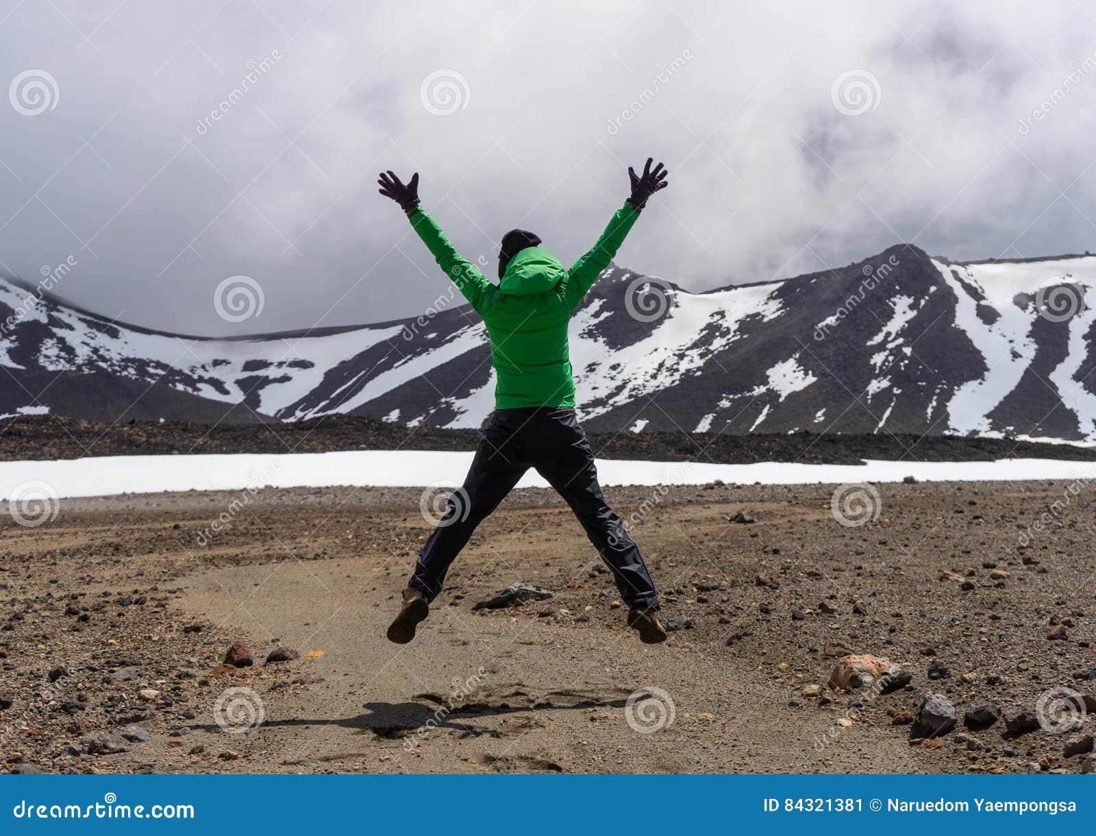 Gelukkige vrouwenwandelaar die in het nationale park van Tongariro springen