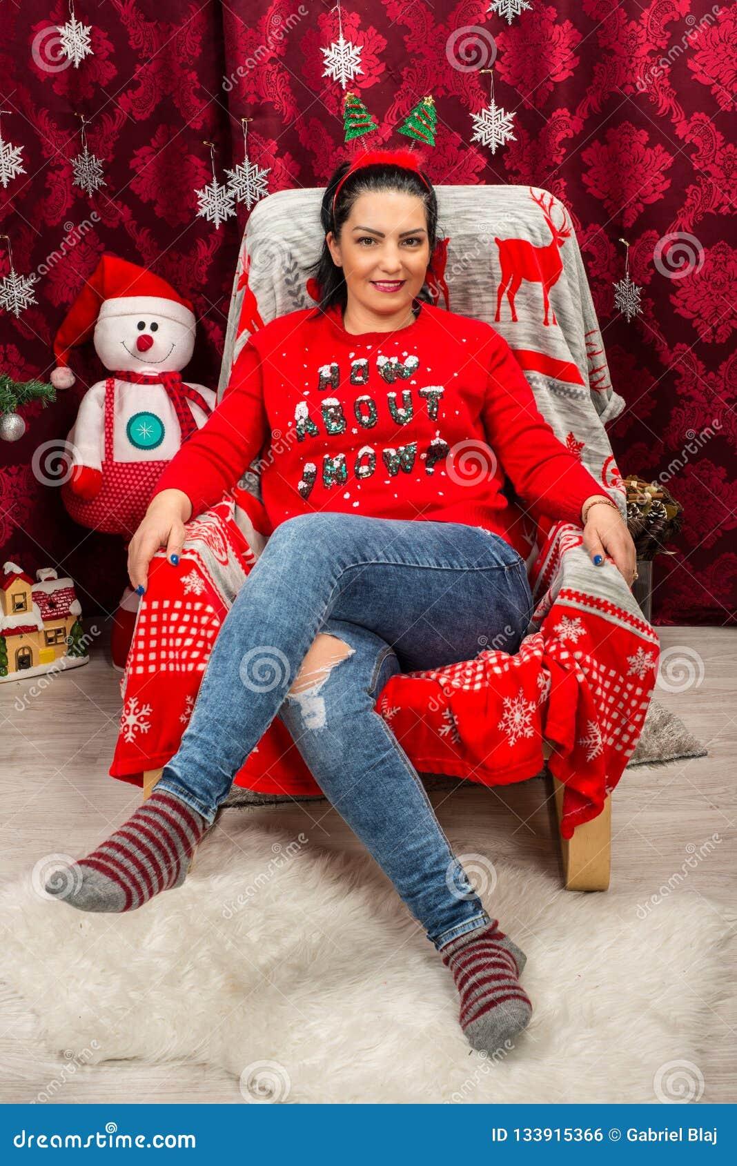 Gelukkige vrouwenzitting op stoel met Kerstboom