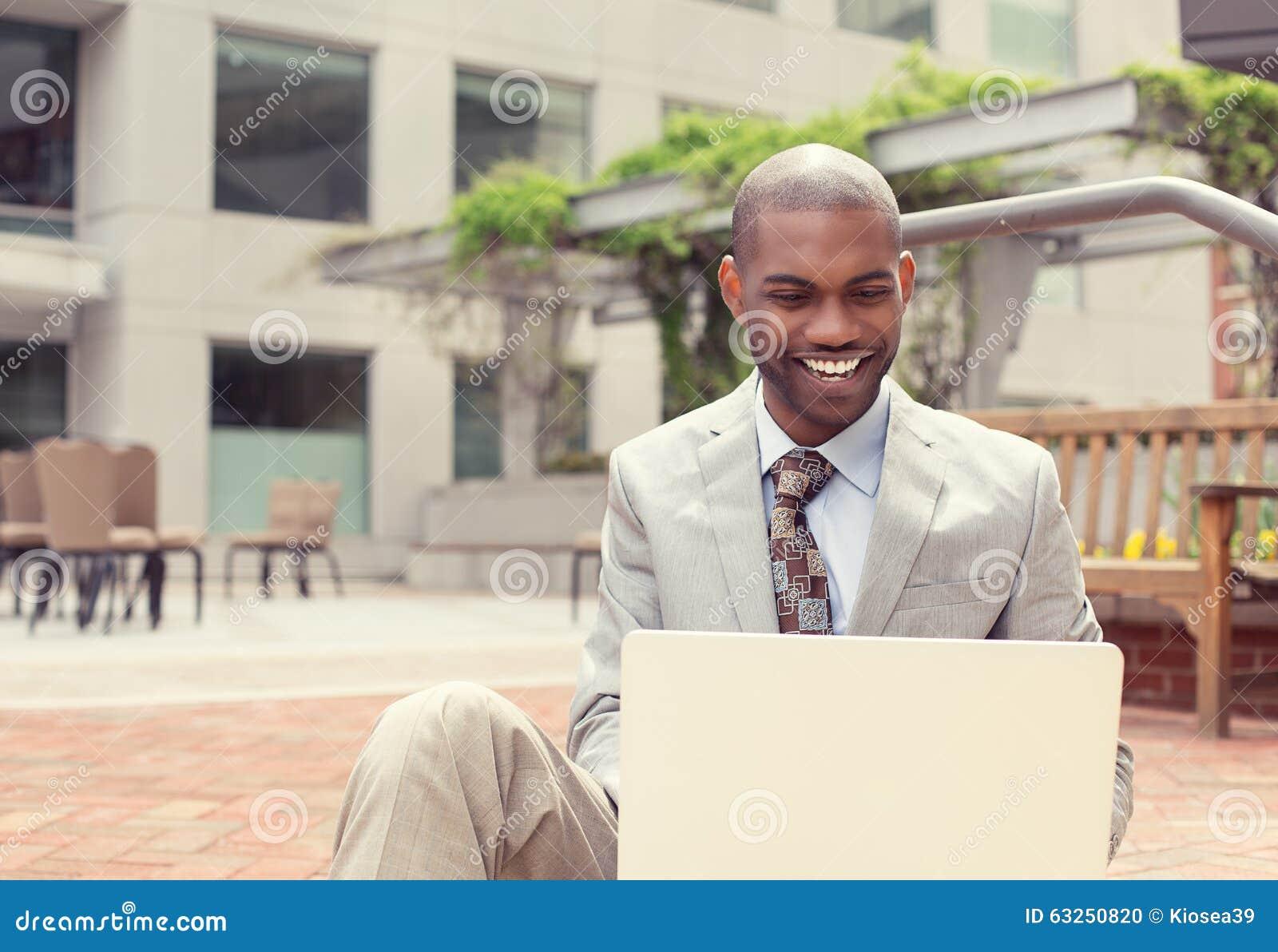 Gelukkige zakenman die aan laptop computer in openlucht werken