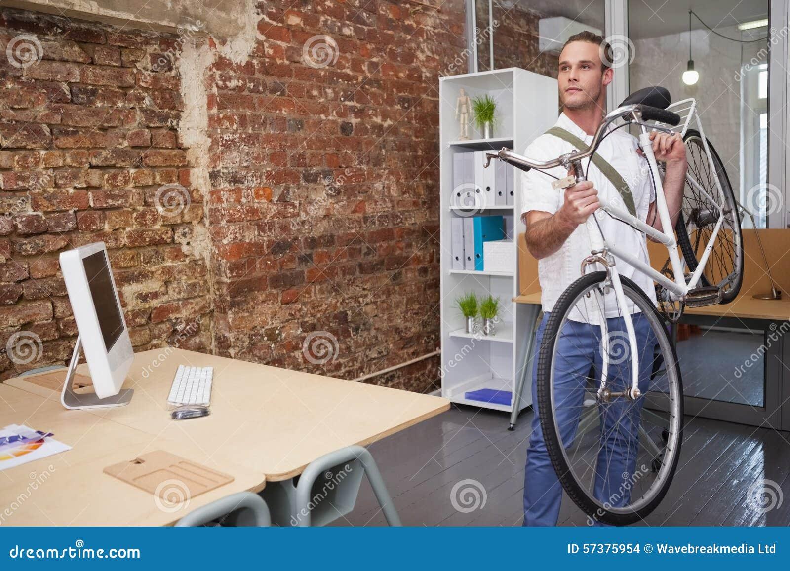 Gelukkige zakenman die zijn fiets dragen