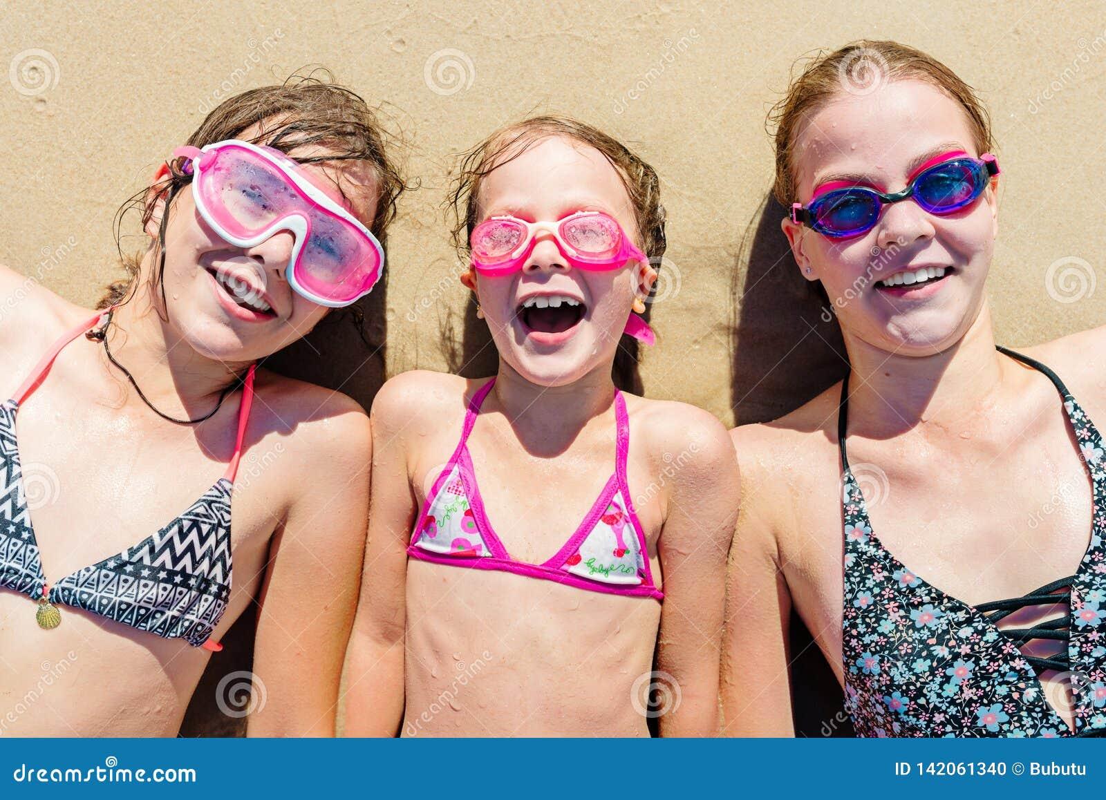 Gelukkige zusters die pret op het strand hebben De zomervakantie en reisconcept