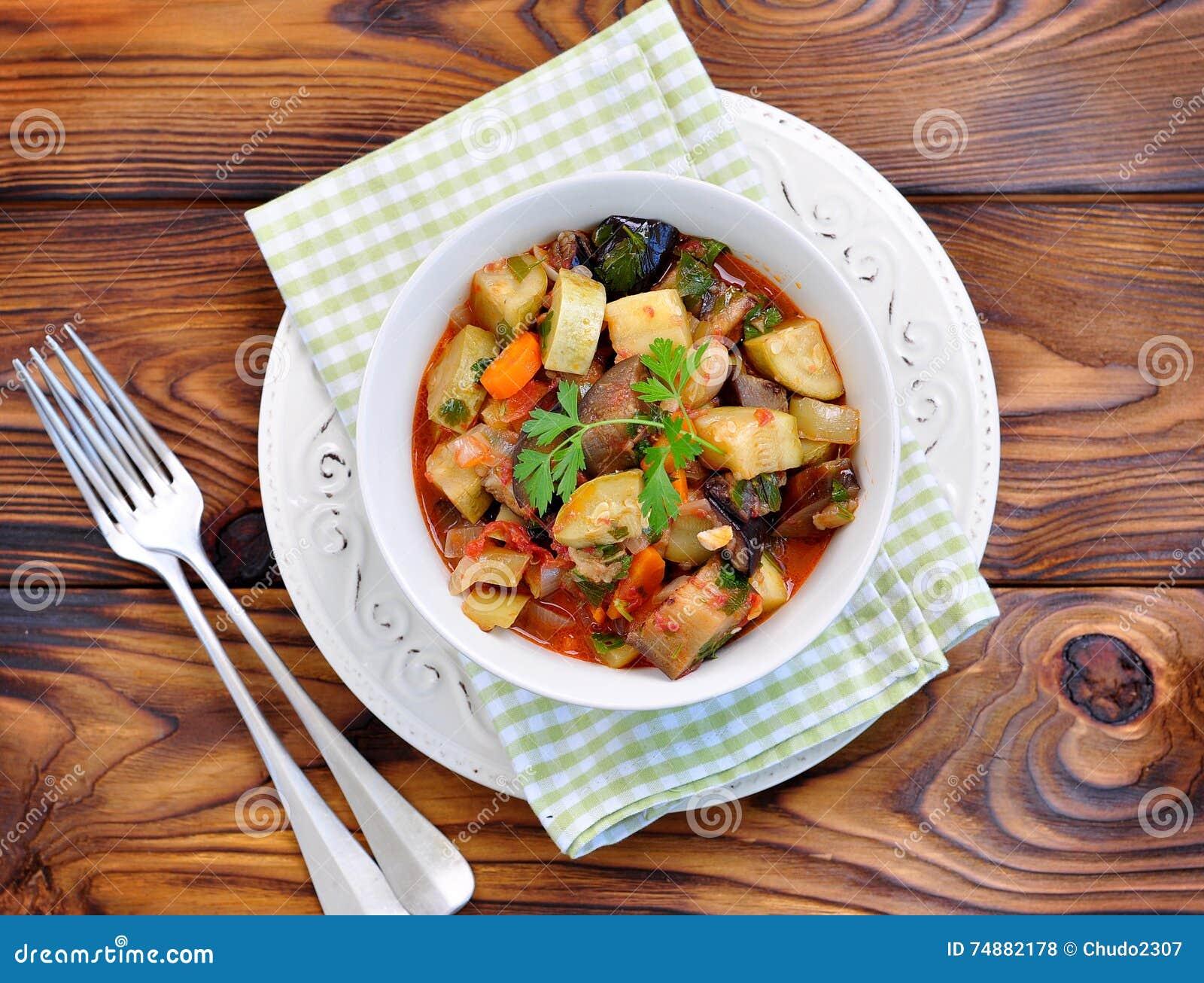 Gemüseeintopfgericht der Aubergine, der Zucchini, der Zwiebeln, der Karotten, der Tomaten, des Knoblauchs und der Petersilie