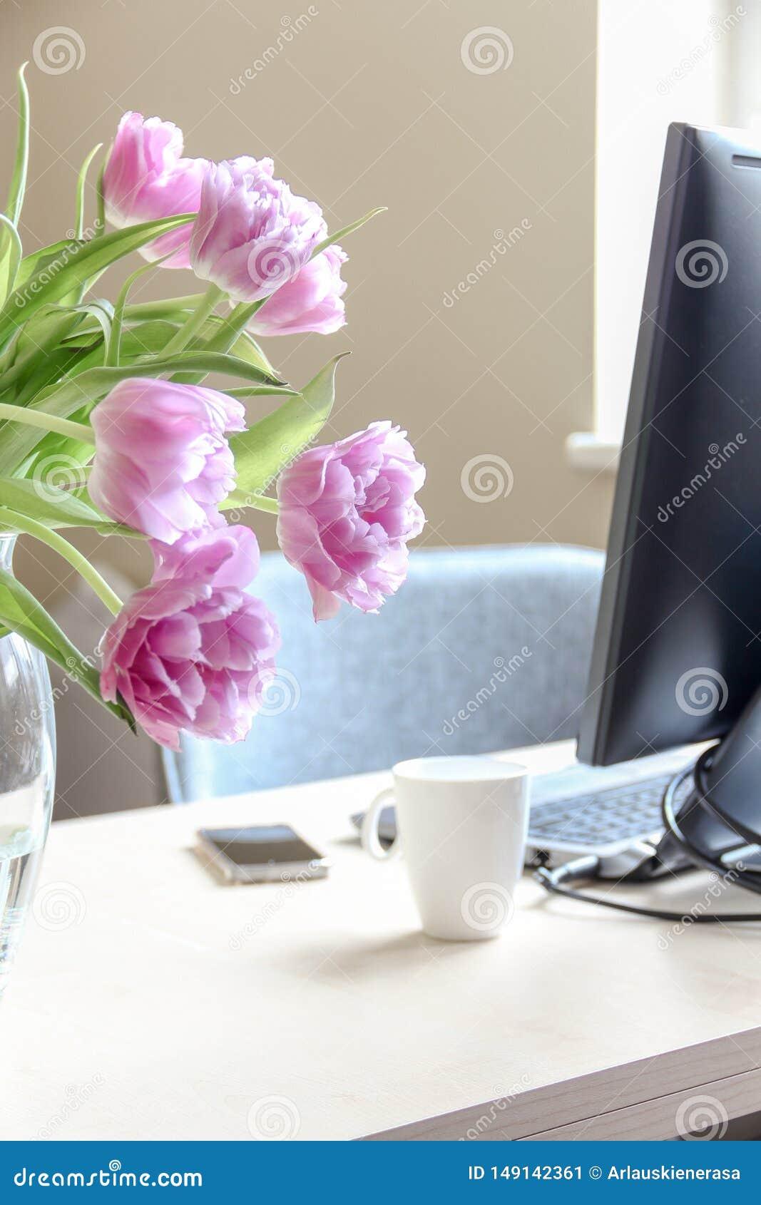Gem?tlicher Arbeitsraum und ein Blumenstrau? von rosa Tulpen in einem Vase