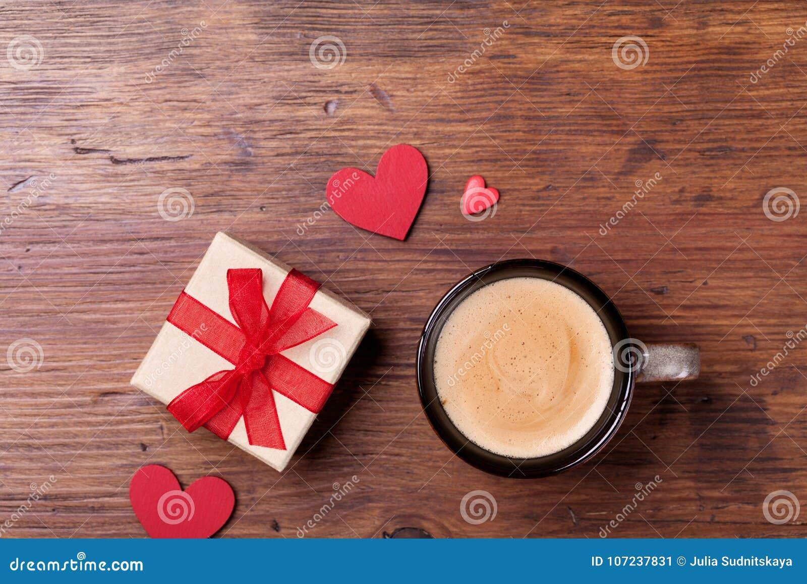 Gemütliches Frühstück für Valentinsgrußtag Kaffee, Geschenk oder Präsentkarton und rotes Herz auf rustikaler Draufsicht des Holzt
