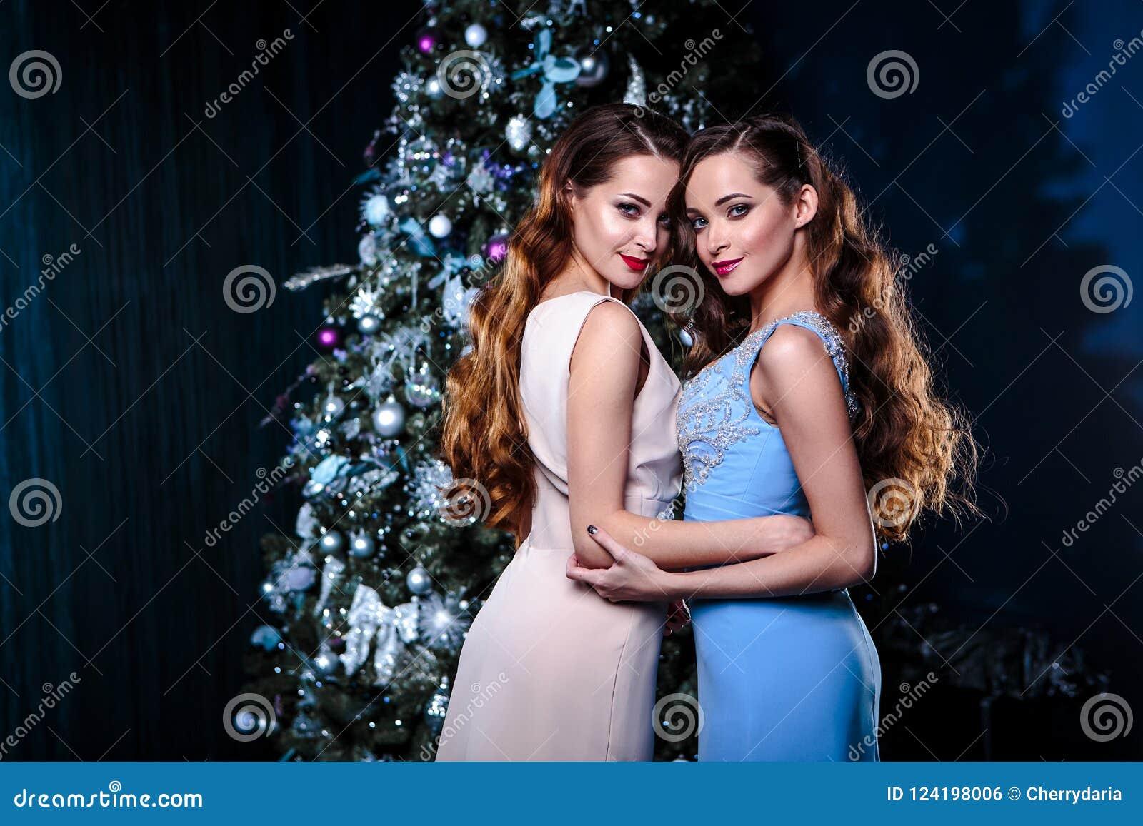c248d27bbcb7 Gemella Le Giovani Donne In Vestiti Da Sera Sopra Il Fondo Di Natale ...
