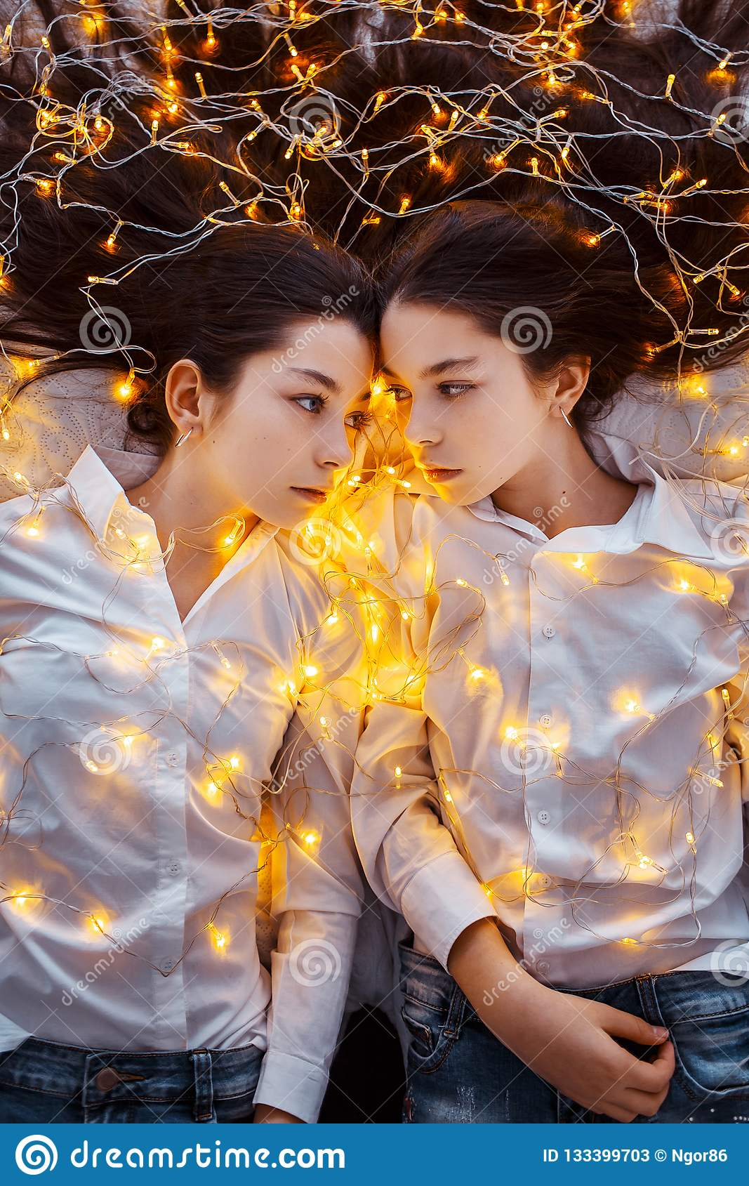Gemelli delle ragazze con le luci ` S EVE del nuovo anno Natale Festa accogliente all abete con le luci e la decorazione dell oro