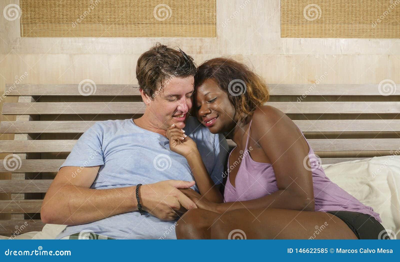 Gemengd het behoren tot een bepaald raspaar in liefde geknuffel samen thuis in bed met mooie speelse zwarte afro Amerikaanse vrou