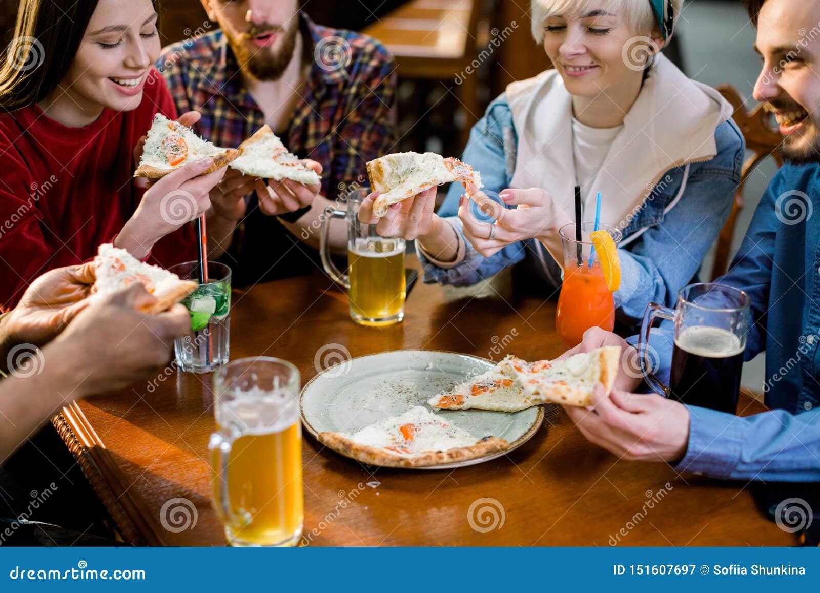Gemischtrassige glückliche junge Leute, die Pizza in der Pizzeria, nette Freunde lachen essen, die Mahlzeit genießend, die das Sp