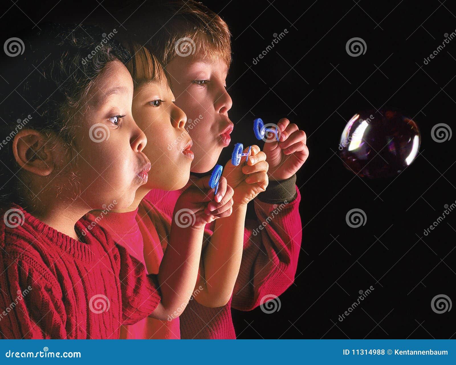 Gemischtrassige Kinder, die Luftblase durchbrennen