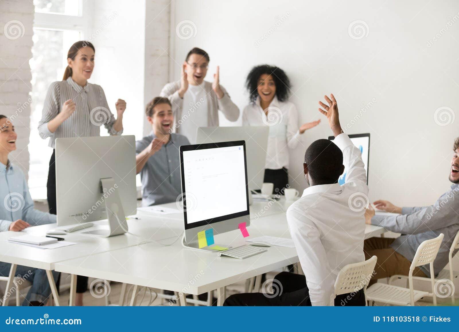 Gemischtrassiges Arbeitsteam, das schwarzen Kollegen mit busine beglückwünscht