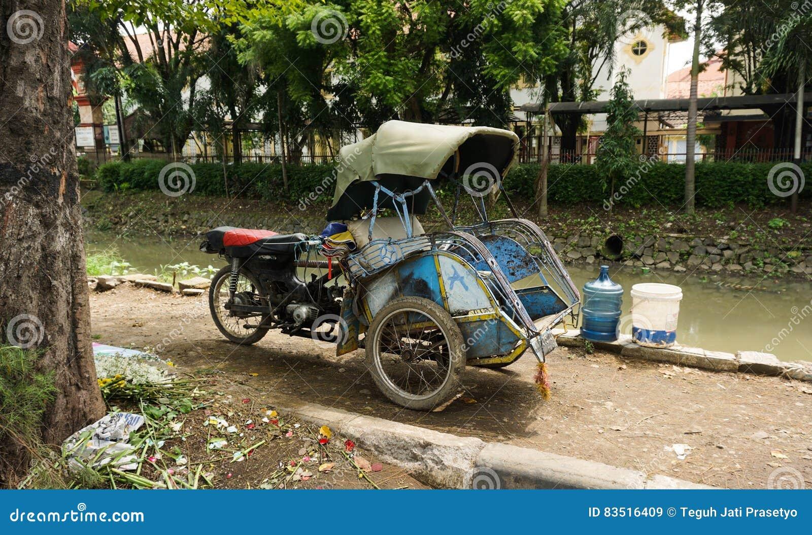 Gemotoriseerde driewielersparken naast een vuile die rivierfoto in Semarang Indonesië wordt genomen