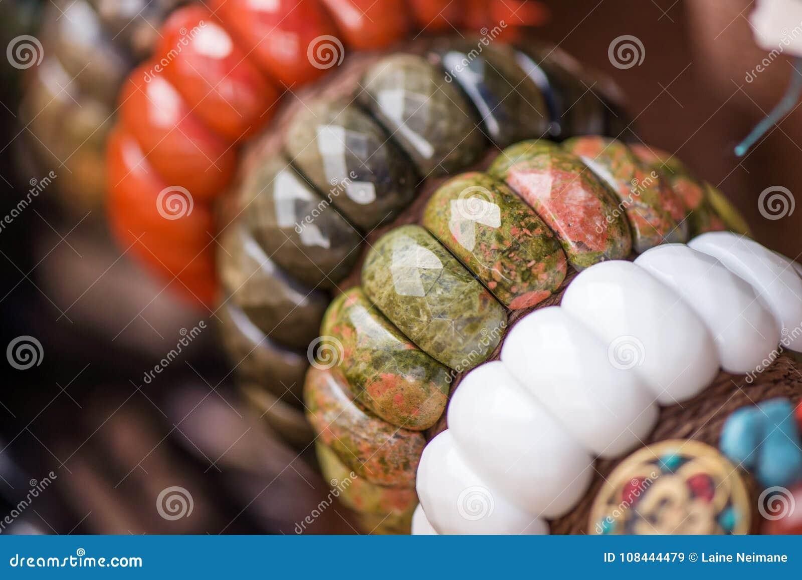 Gemstonearmband och halsband i rad Smycken som göras av den röda jaspisen, unakitestenar, obsidianstenar och den vita onyxstenen