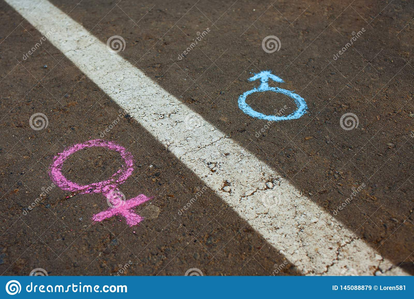 Gender symbols or signs for male and female drawn with chalk on asphalt. The concept of gender equality
