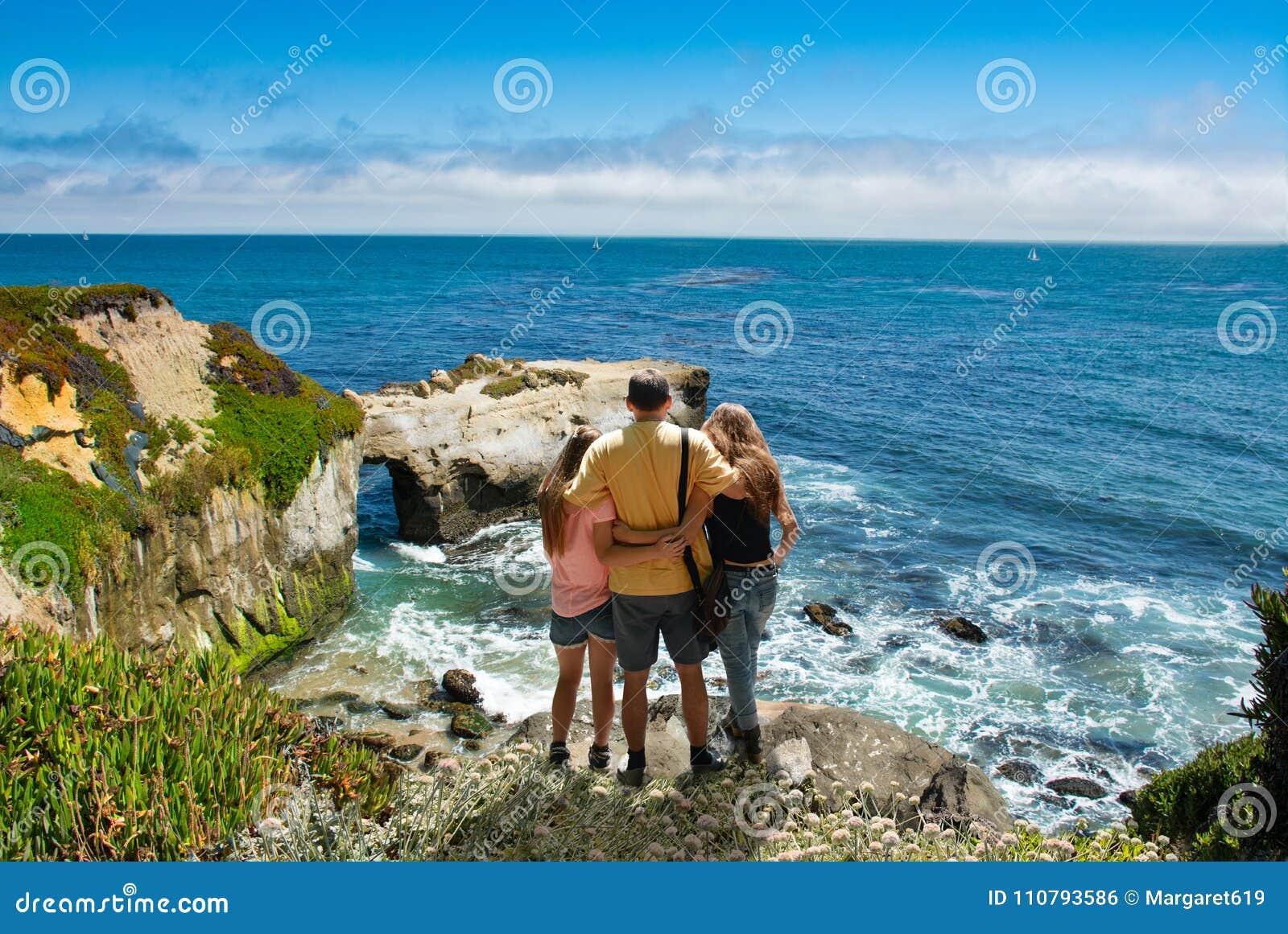 Gene com os braços em torno de sua família que olha a vista para o mar bonita