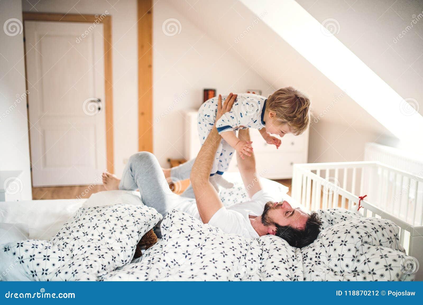 Gene com um menino da criança que tem o divertimento no quarto em casa em horas de dormir