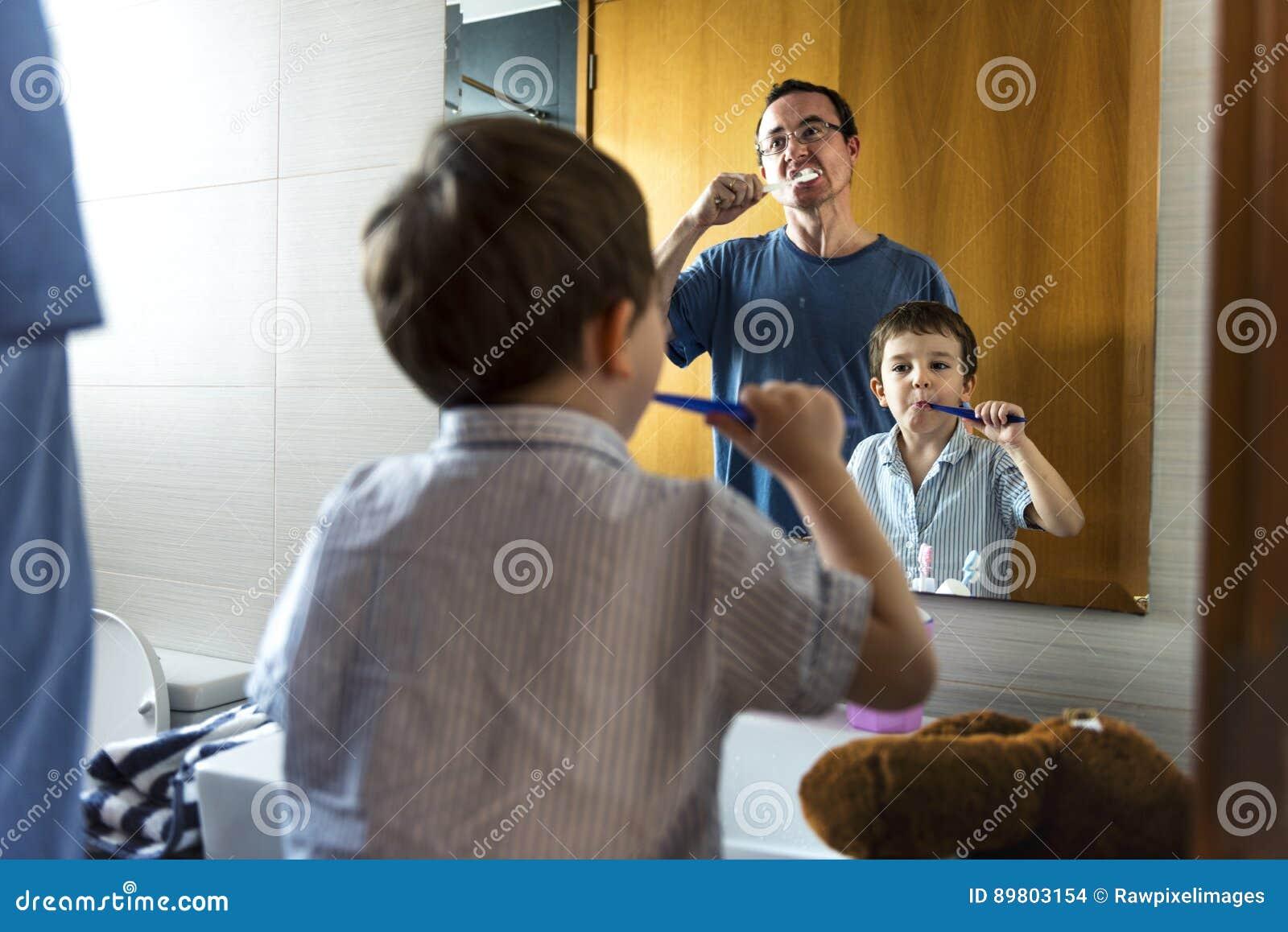 Gene ensinando ao filho como escovar seus dentes