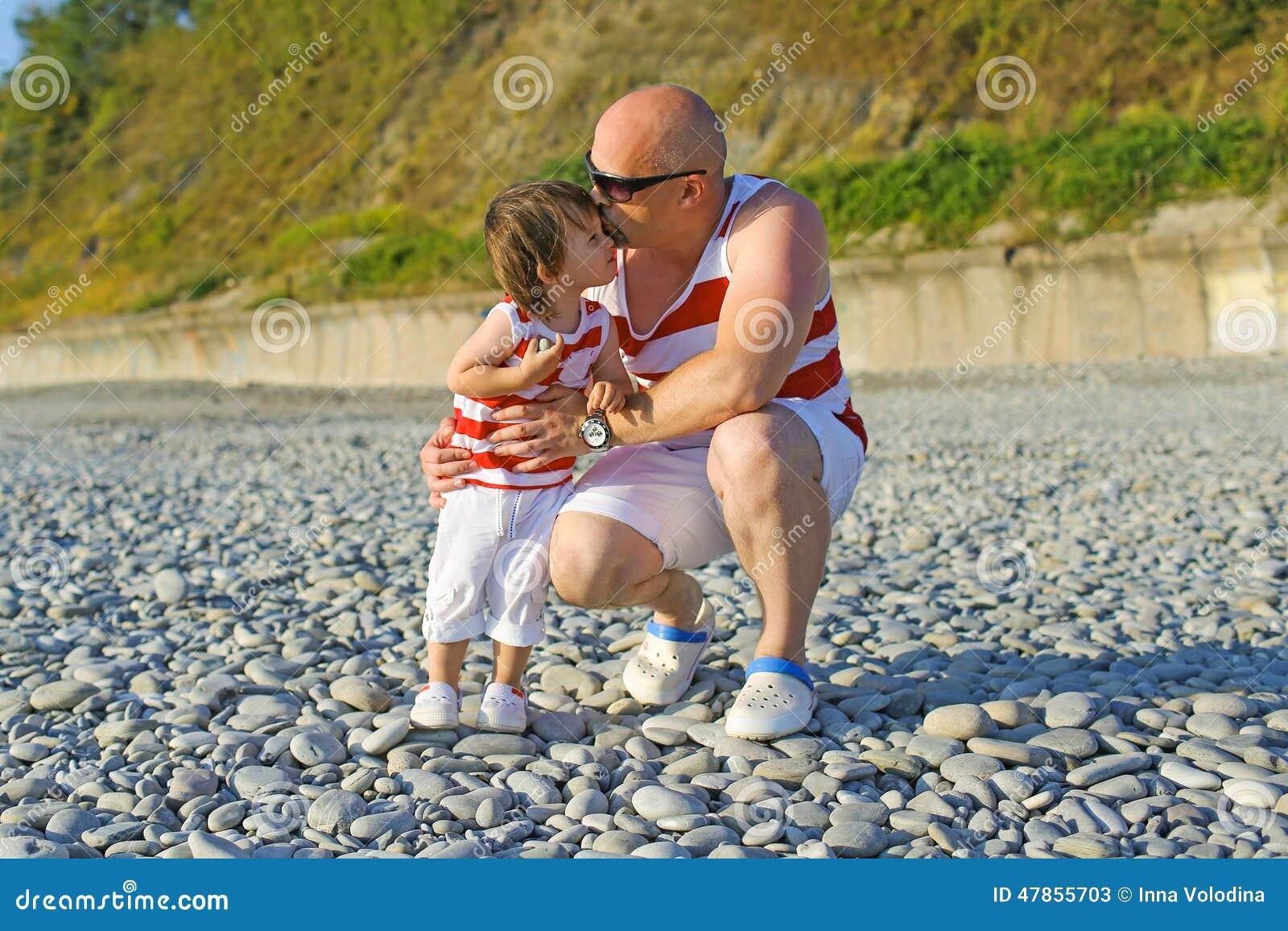Generi baciare i suoi 2 anni di figlio in simili vestiti sulla spiaggia