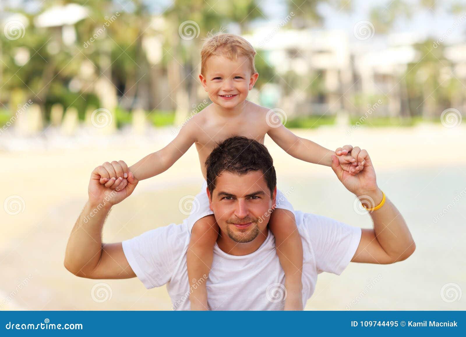Generi divertiresi sulla spiaggia con il suo piccolo figlio