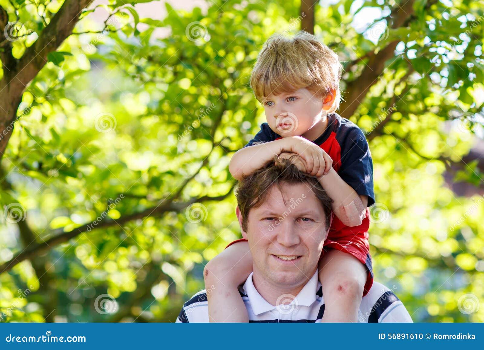 Generi il bambino di trasporto sulle sue spalle nel parco