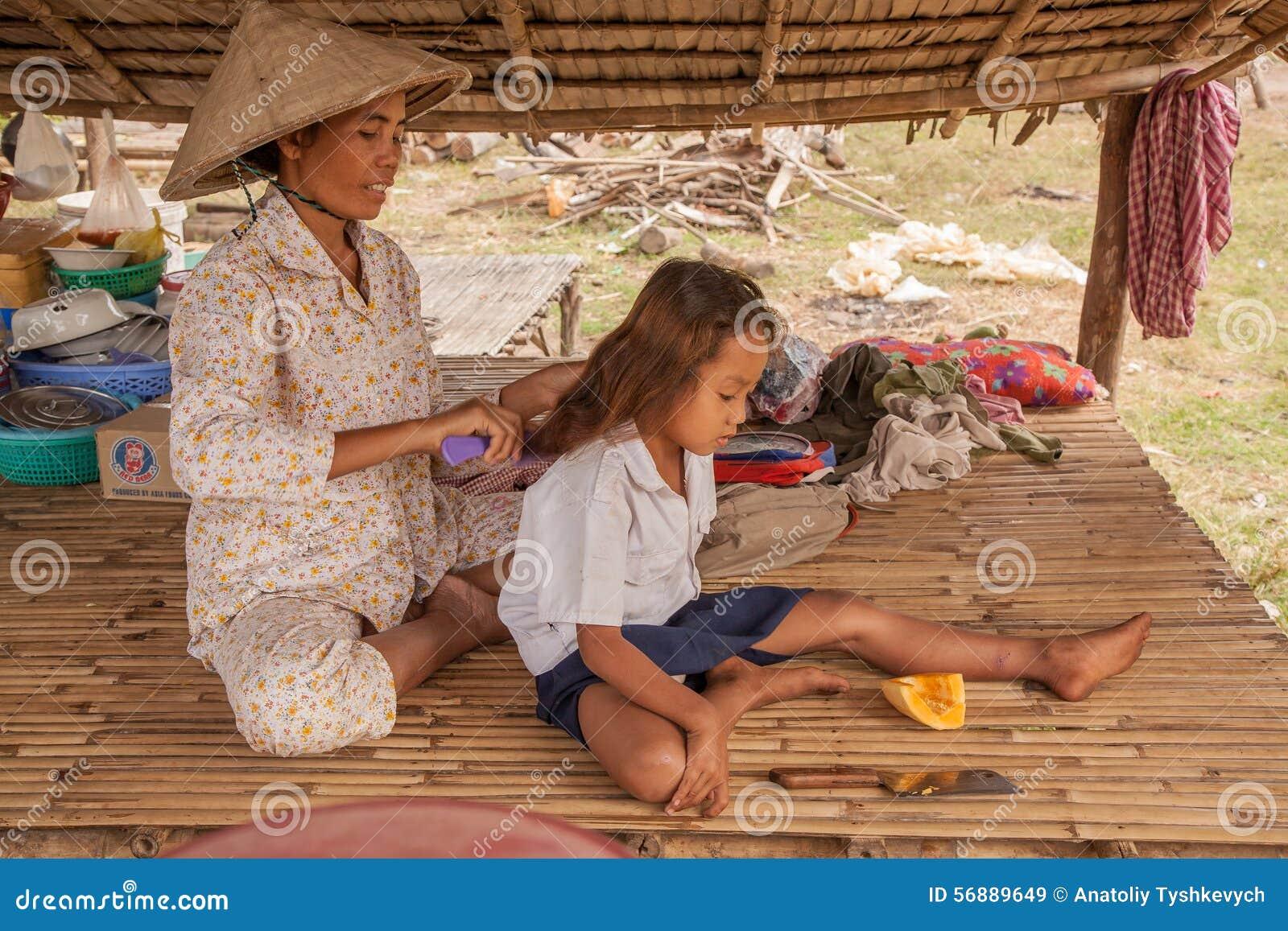 Generi la pettinatura della figlia su una chaise-lounge sotto un baldacchino