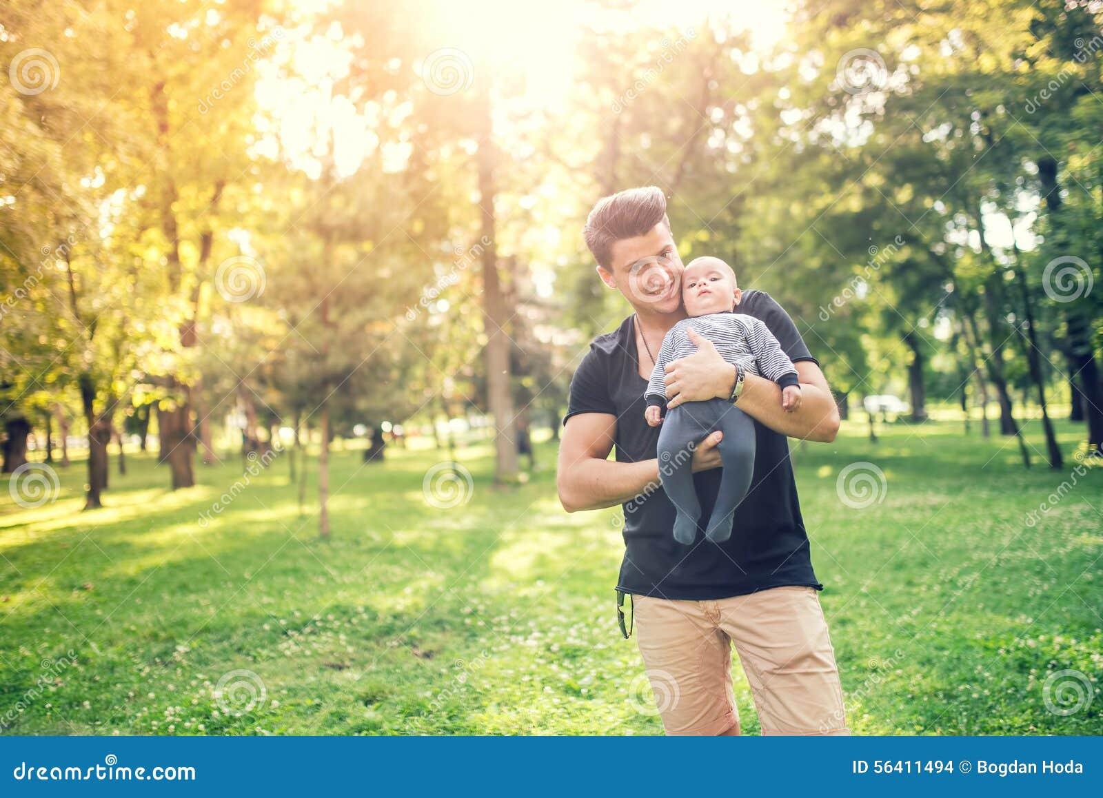Generi la tenuta del figlio piccolo, ragazzo infantile un giorno soleggiato in parco