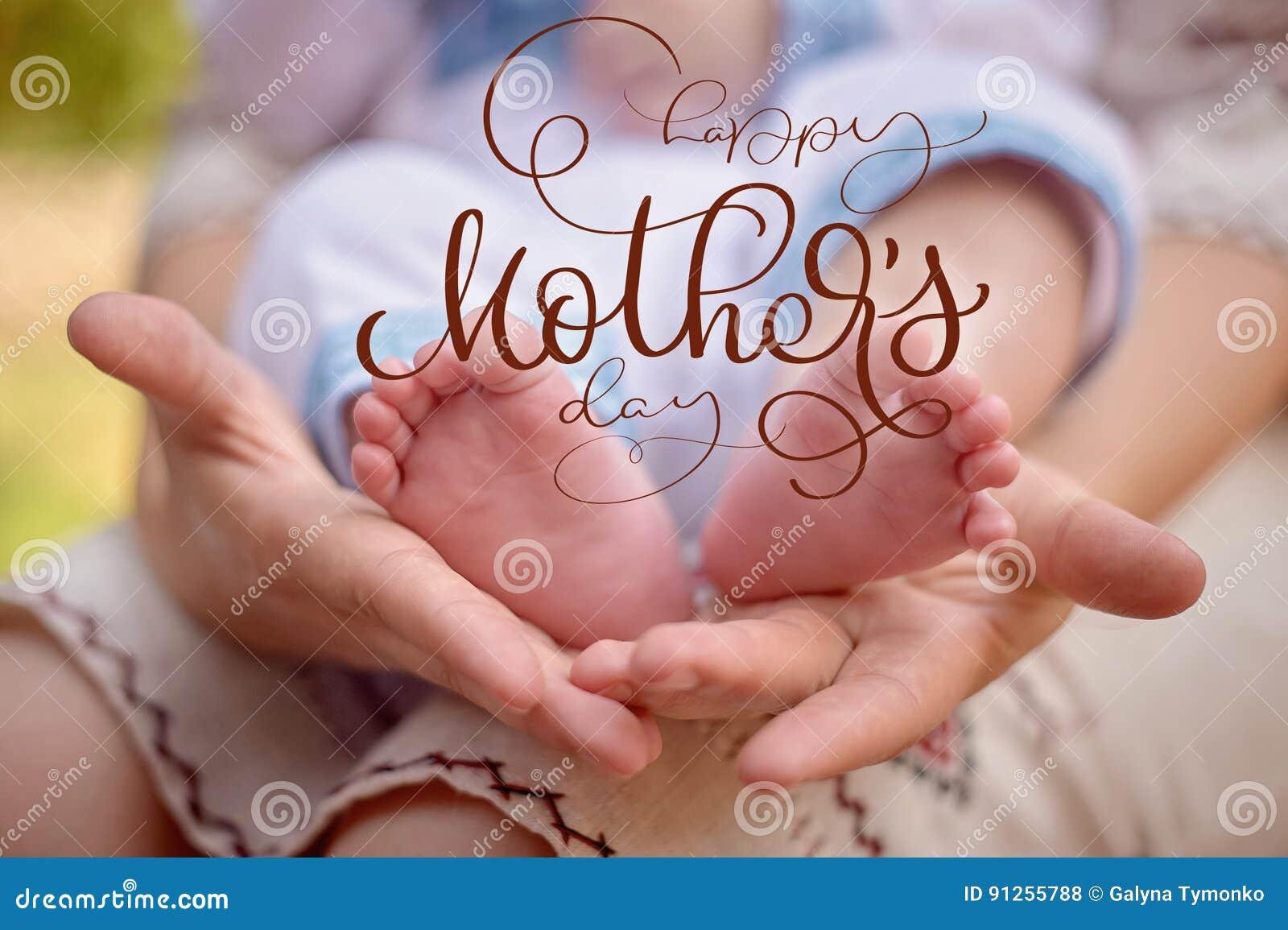 Generi la tenuta i piedi del suoi figlio neonato e testo felice del giorno di madri Tiraggio della mano dell iscrizione di callig