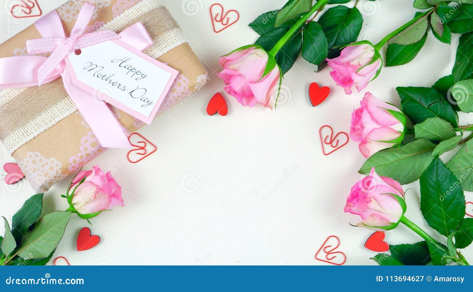 Generi le spese generali del giorno del ` s con il regalo e le rose rosa sul fondo di legno bianco della tavola
