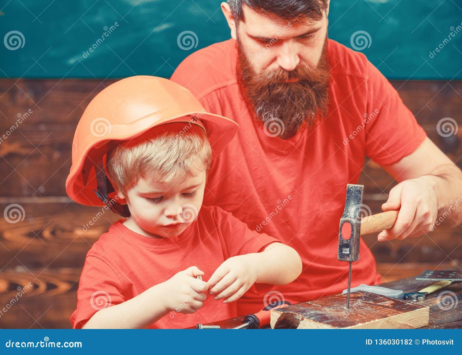 Generi, parent con la barba che insegna al piccolo figlio ad utilizzare le bullette per suole ed il martello Ragazzo, bambino occ