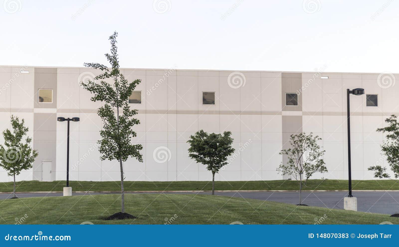 Generischer Lager-Bürokomplex Buildilng mit grünem Rasen und Straßenbeleuchtung