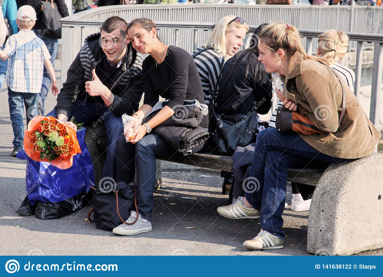 Geneva, Switzerland - May, 2012: The group of young people sitting on the street bench in front of the river. Couple of friend, ma