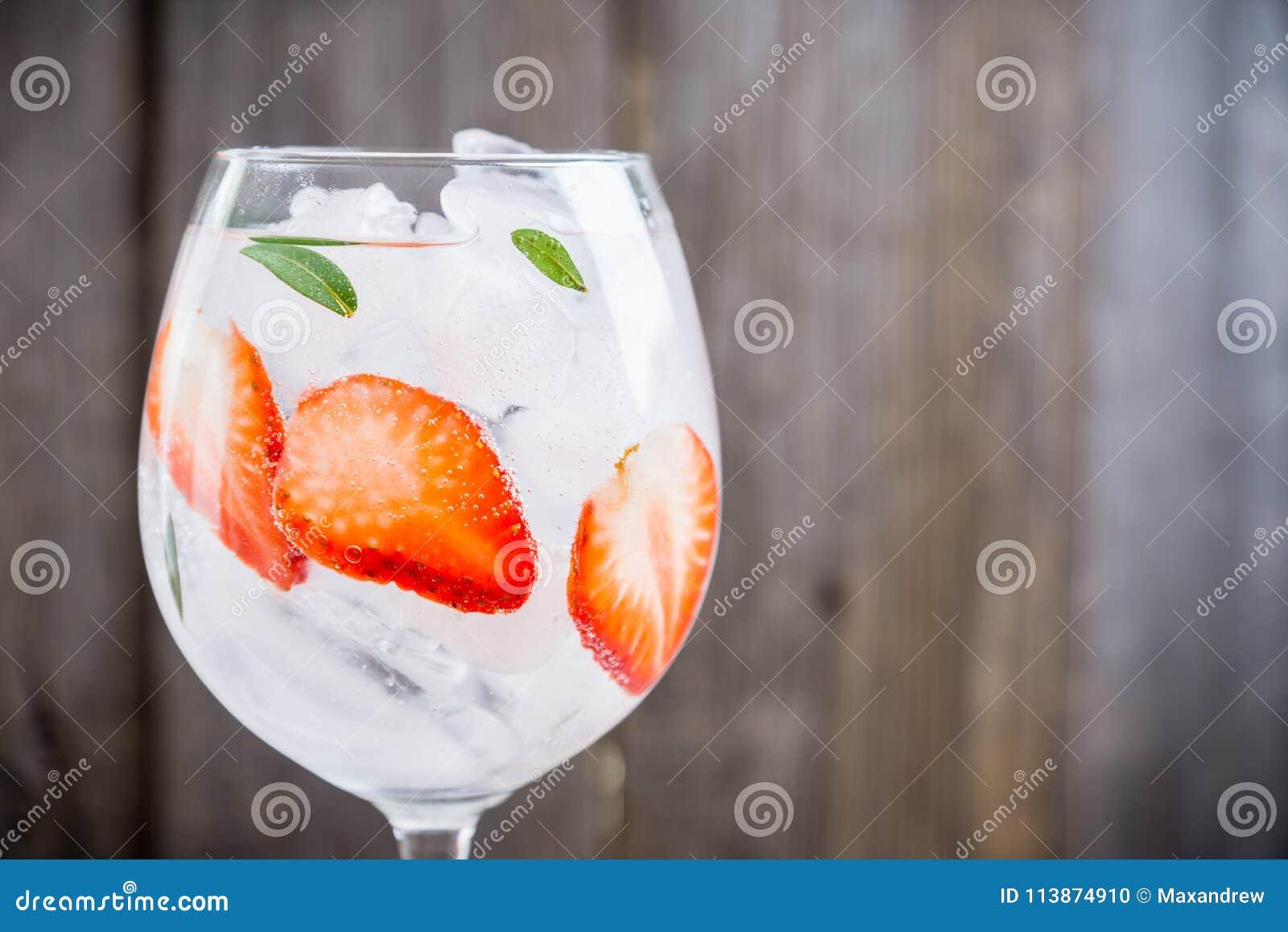 Genièvre avec la fraise et la glace en verre de vin