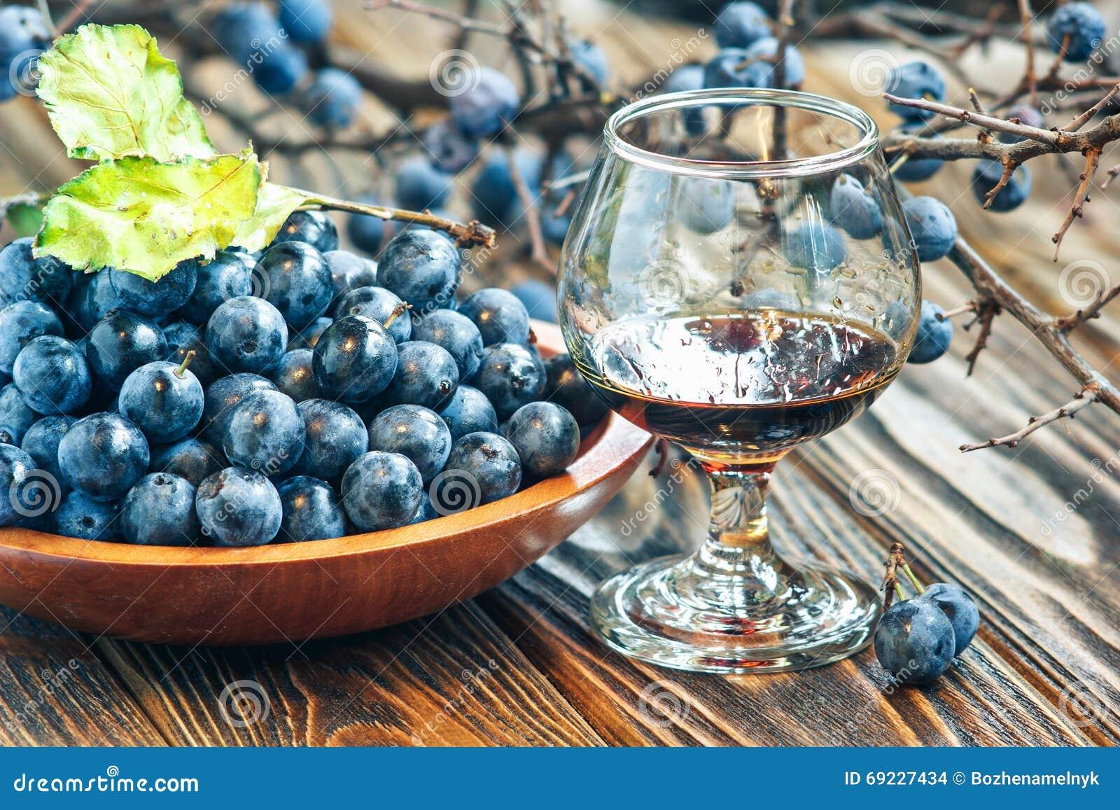 Genièvre de prunellier Verre de liquide brun-rougeâtre doux léger fait maison de prunellier liqueur ou vin au parfum de prunellie