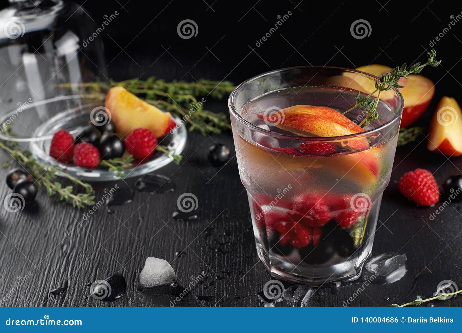 Genièvre de thym de framboise et cocktail de tonique avec le cassis et les pêches