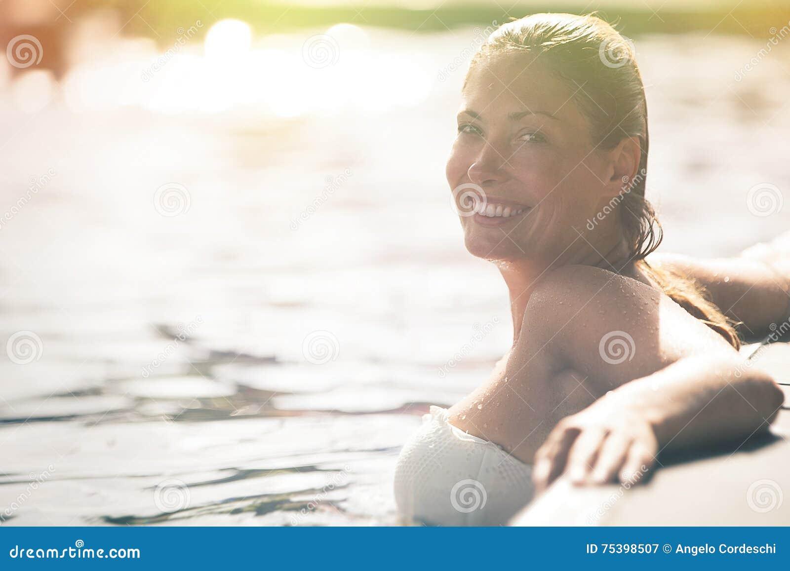 Genießen Sie den Sommer Frau, die im Poolwasser sich entspannt