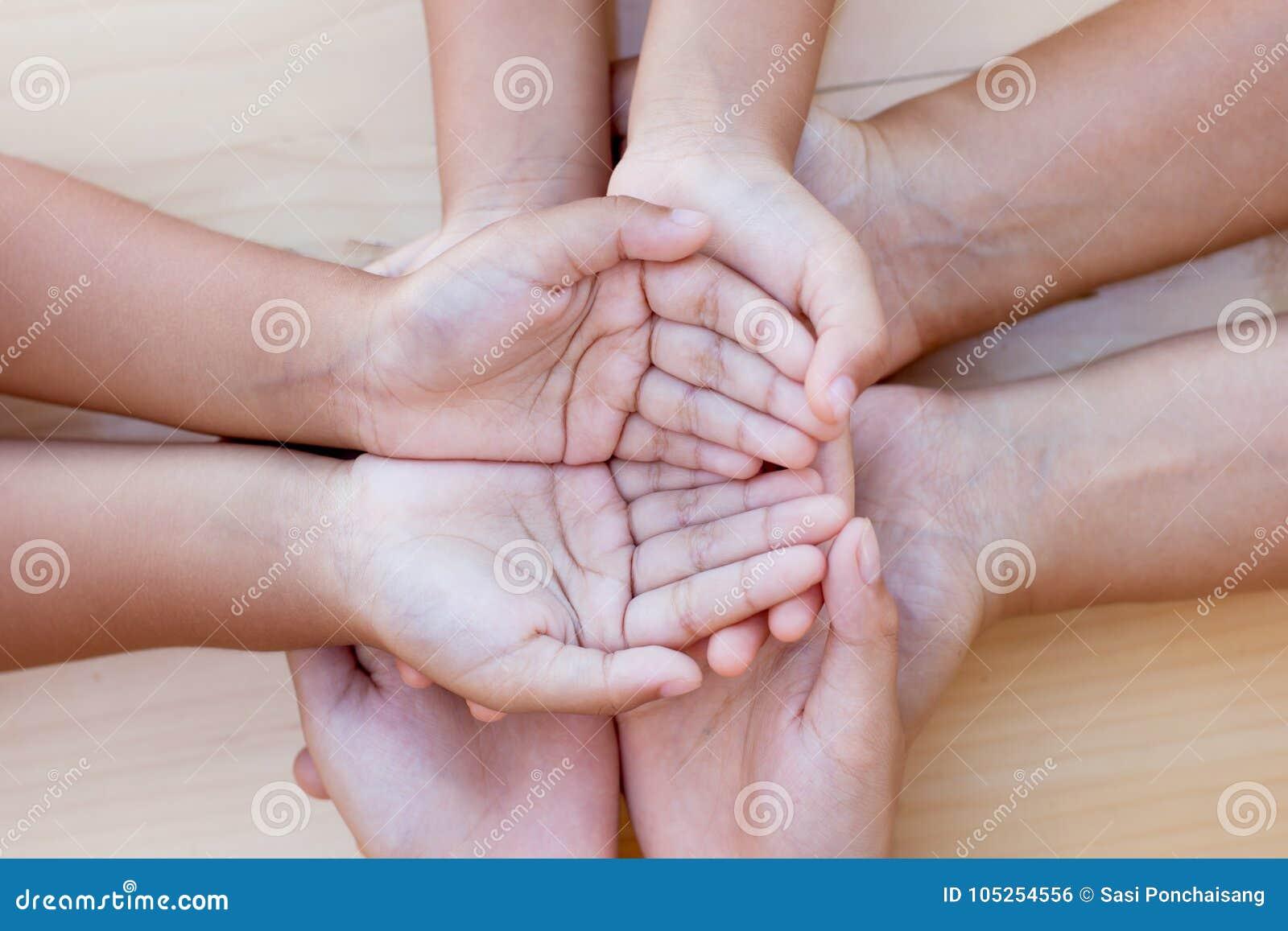 Genitore e bambini che si tengono per mano insieme sul fondo di legno