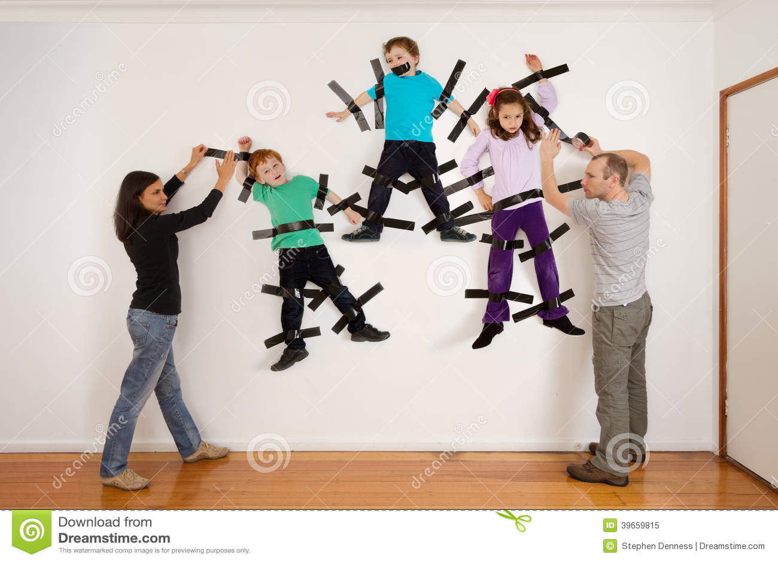 Genitori che attaccano i bambini allo scherzo della parete