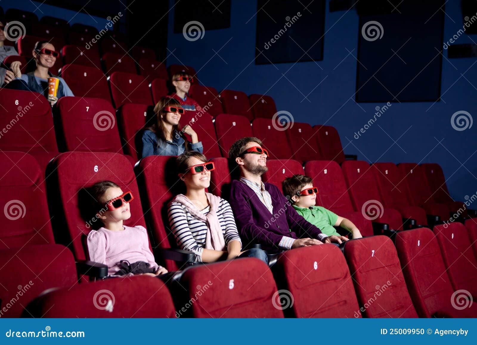 Genitori con i bambini che guardano una commedia