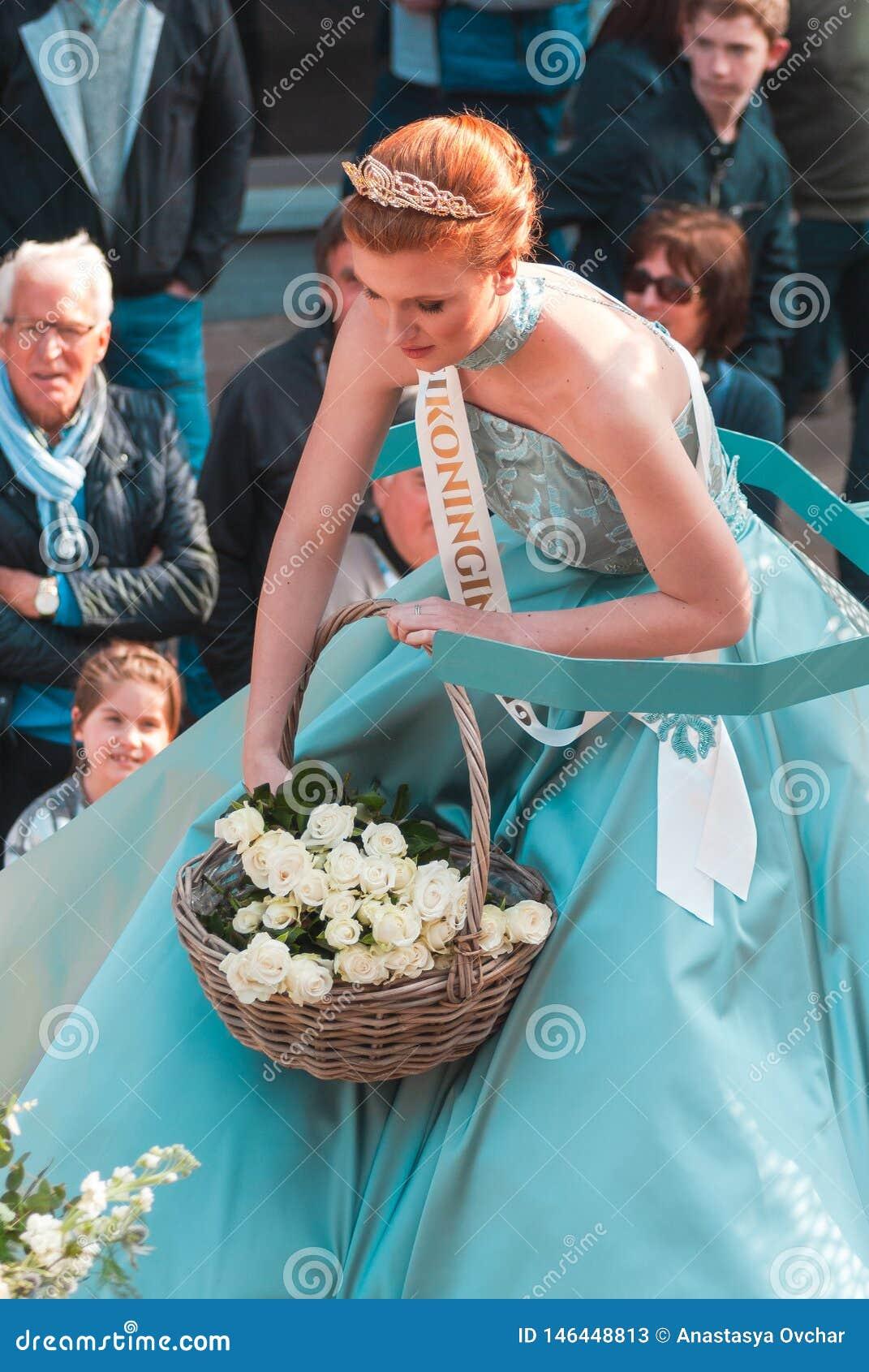 Genk, Bélgica - 1 de mayo de 2019: Participantes del O-desfile anual La reina de mayo está lanzando las rosas blancas a la muched