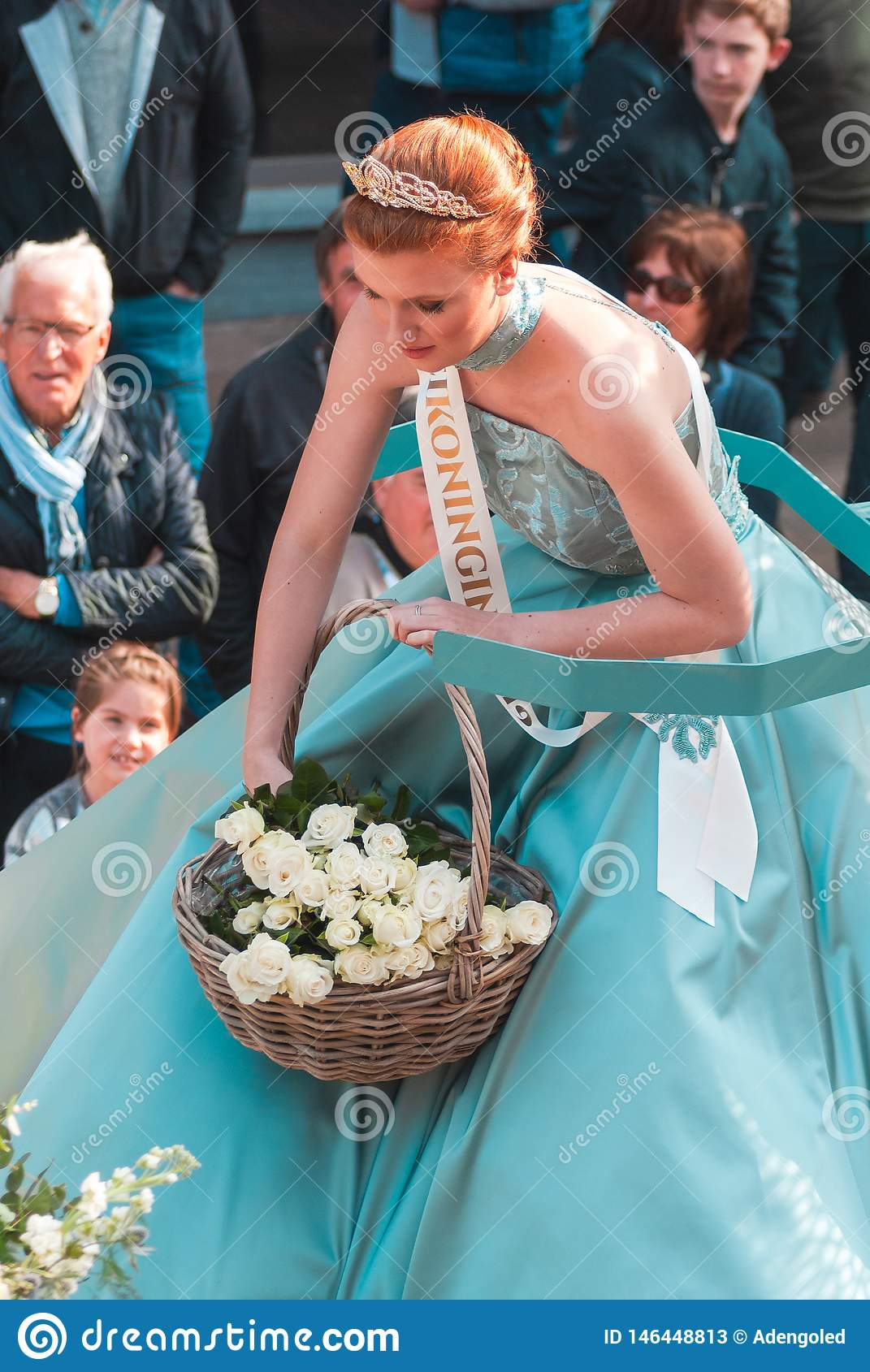 Genk, Belgium - May 1st 2019: Participants of annual O-parade. The queen of May is throwing white roses to the crowd