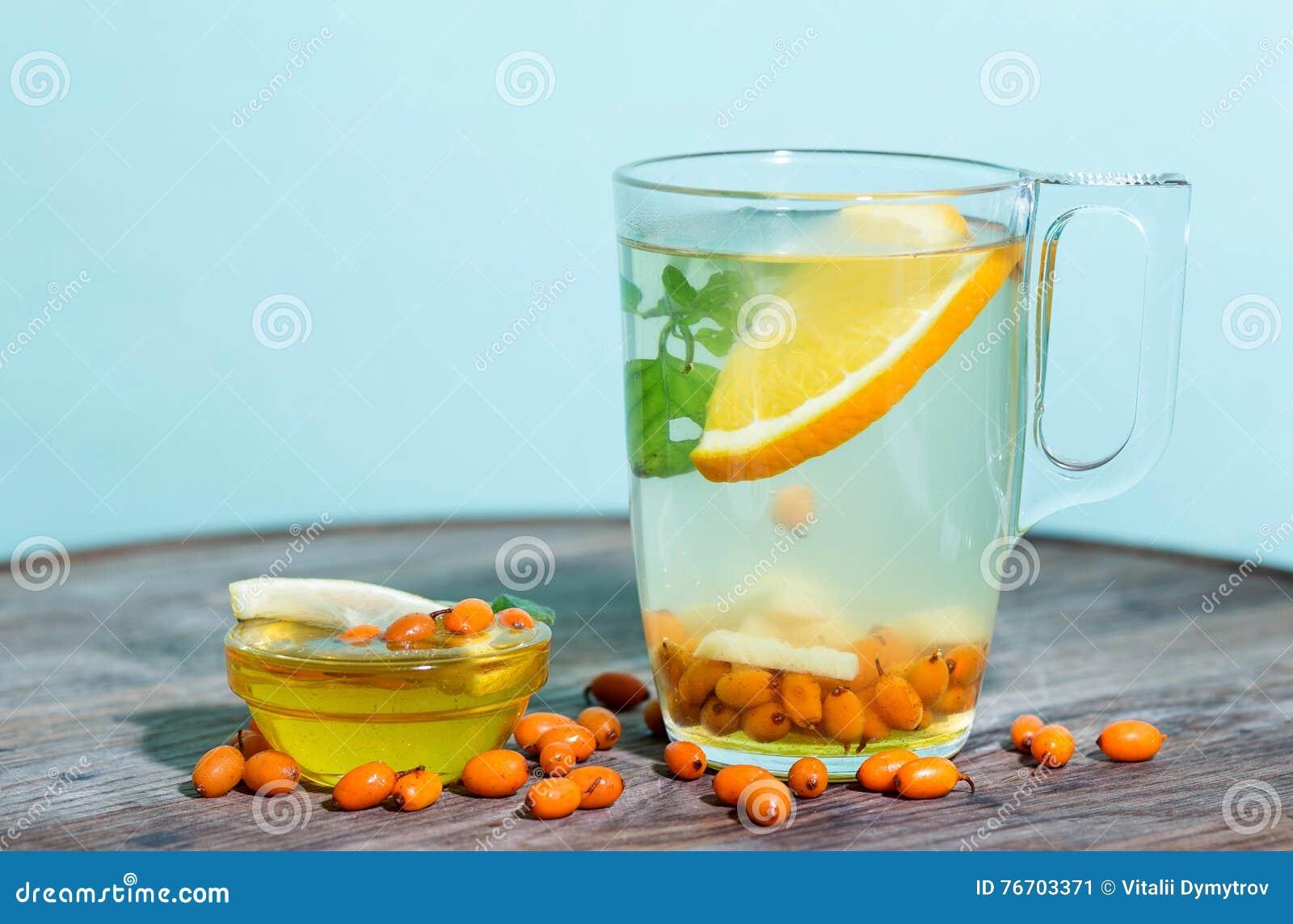 Genomskinlig kopp te med den havsbuckthornen, honung och citronen