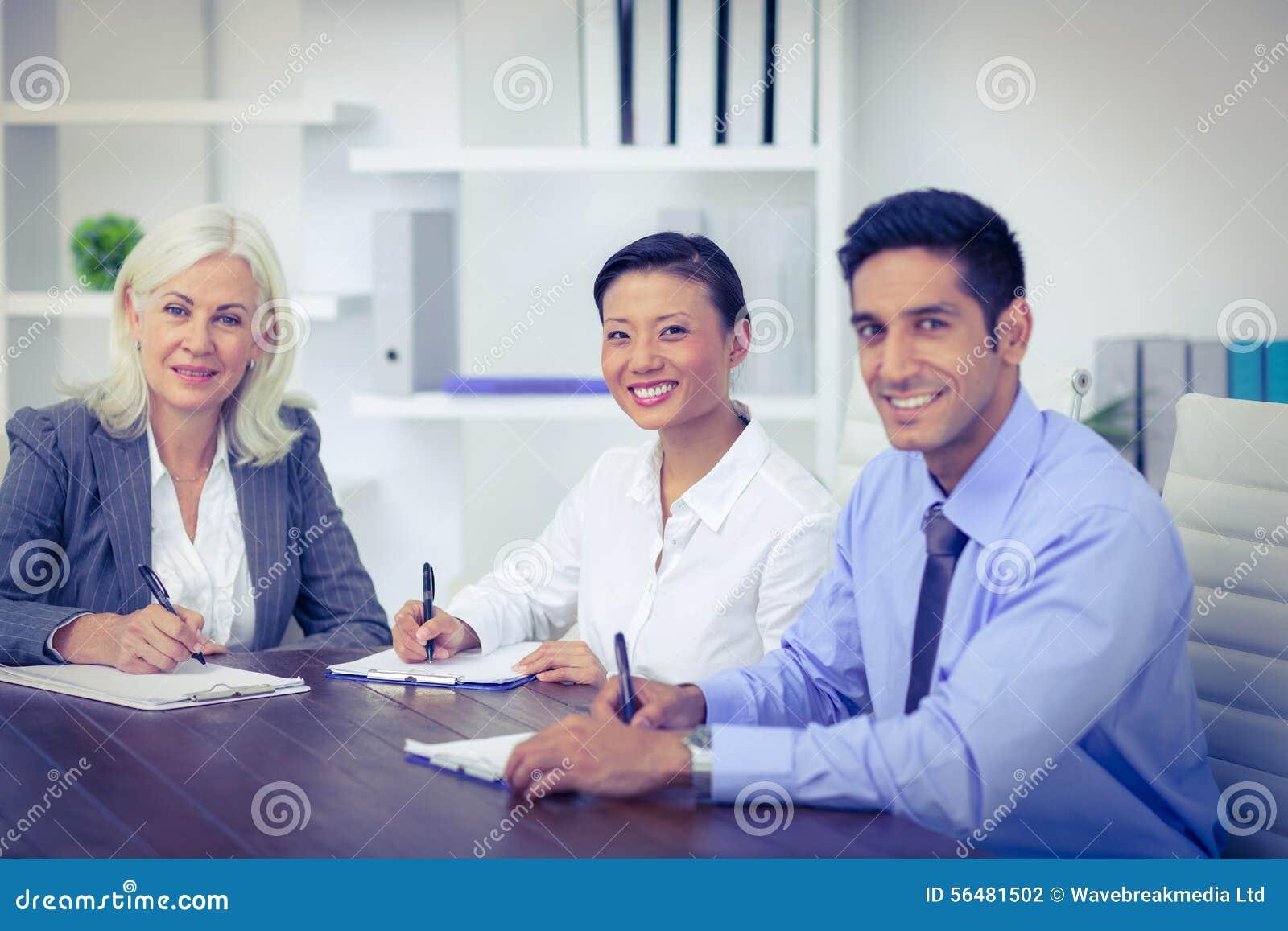 Gens d affaires écrivant sur des presse-papiers et regardant l appareil-photo