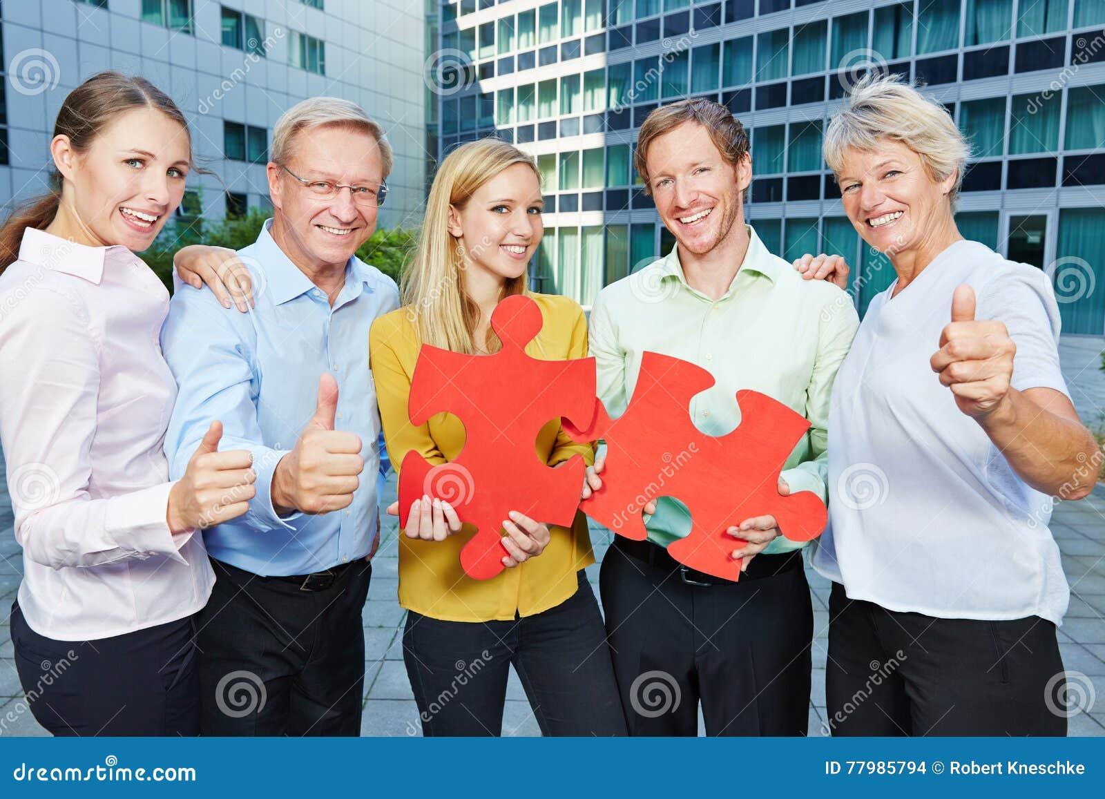 Gens d affaires avec le puzzle de jugsaw tenant des pouces