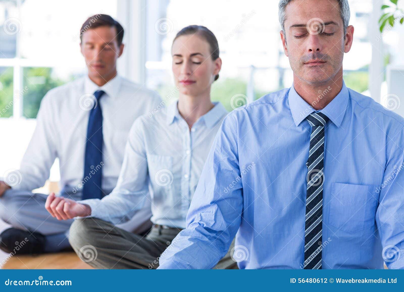 Gens d affaires faisant le yoga sur le plancher