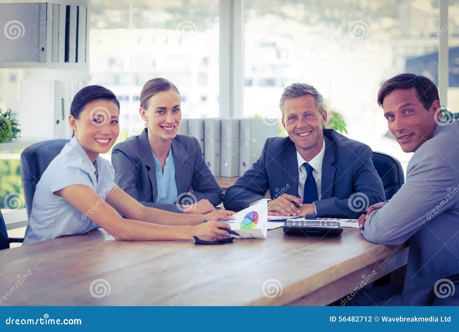 Gens d affaires regardant l appareil-photo au cours de la réunion