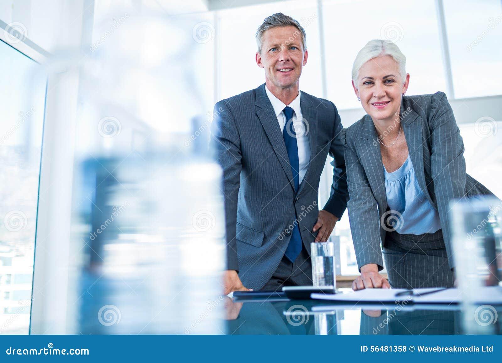 Gens d affaires regardant l appareil-photo derrière le bureau