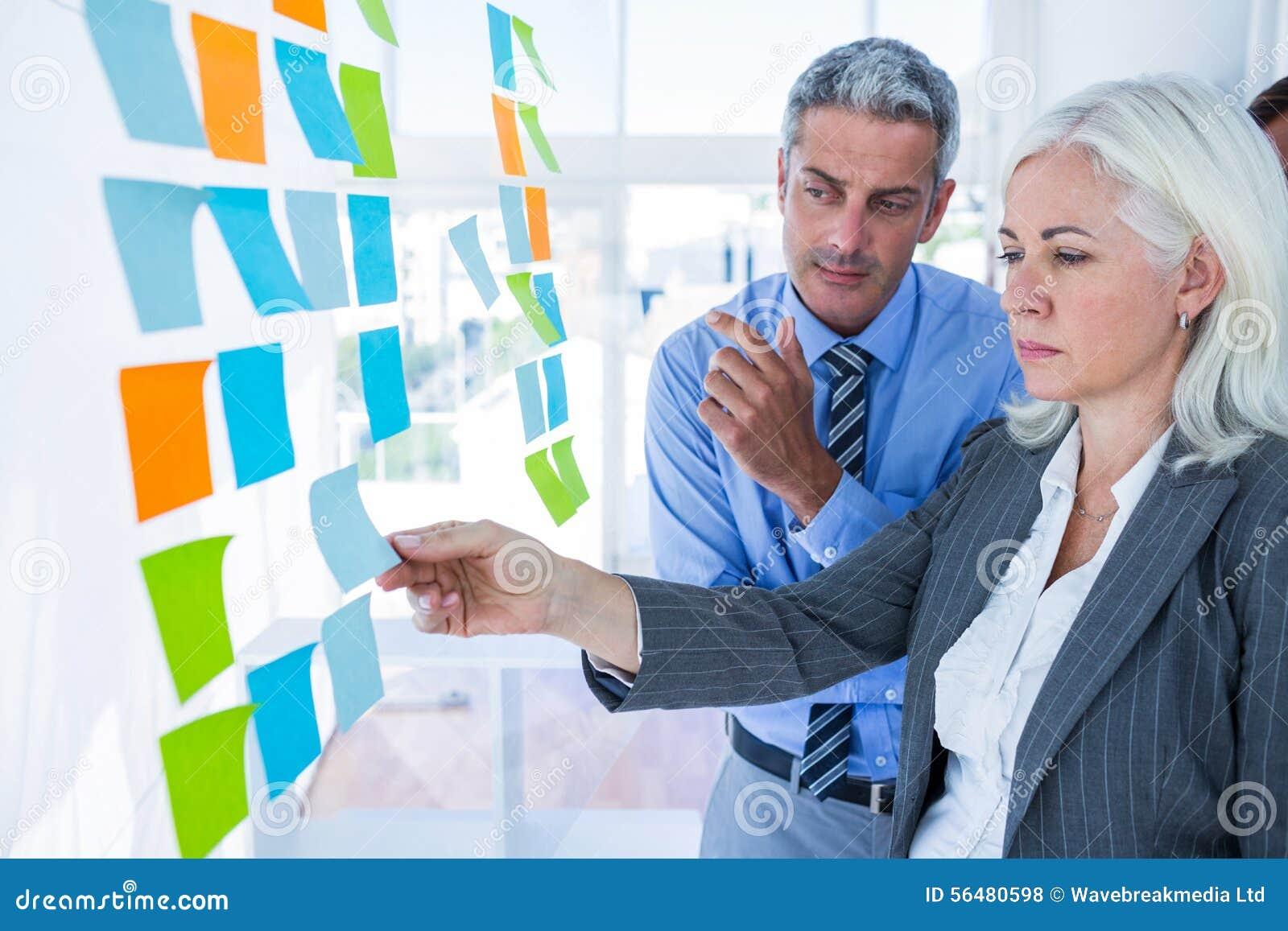 Gens d affaires regardant le post-it sur le mur